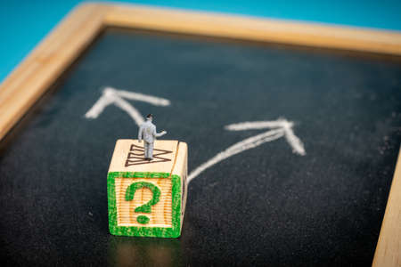 Business concept: Decision making. Miniature man on chalkboard with two arrows pointing at different directions