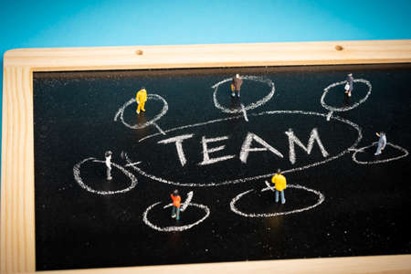Teamwork concept: a group of miniatures person on a chalkboard with Reklamní fotografie