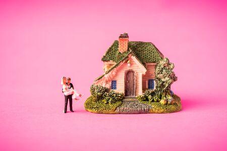 Love concept. Miniature couple against pink background