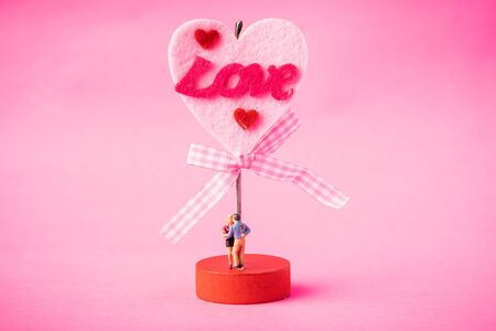Love concept. Miniature couple against pink background