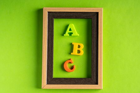 ABC and empty photo frame against green background