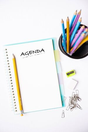 AGENDA wordings on a notebook on a table, flat lay composition, copy space for text