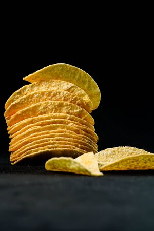 Delicious and crisp potato chips, isolated against black background