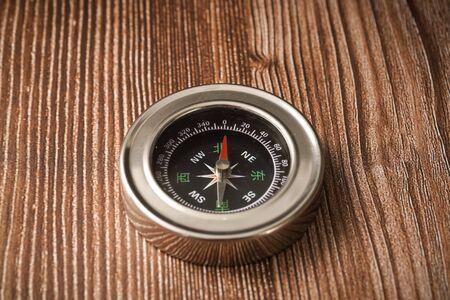 Metallic compass on wooden background