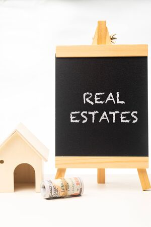 """""""REAL ESTATES"""" wordings on a chalkboard with rolled up money and miniature house"""