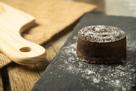 Chocolate fondant with icing sugars on top, on a black slate plate, selective focus