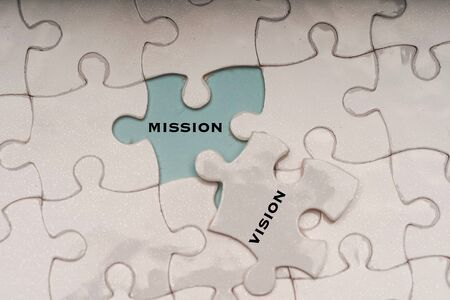 Business management concept: vision and mission wordings on puzzle pieces