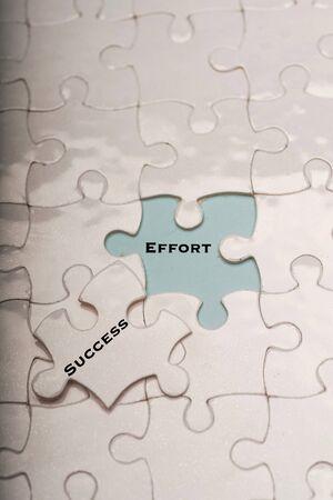 Motivational concept: effort and success wordings on puzzle pieces
