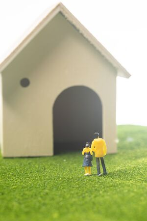 Miniature couple figures in front of a toy house, buying or owning a house concept