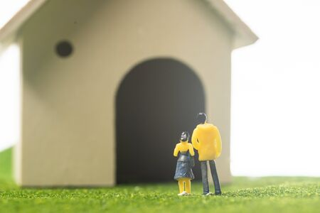 Miniature couple figures in front of a toy house, buying or owning a house concept Stok Fotoğraf