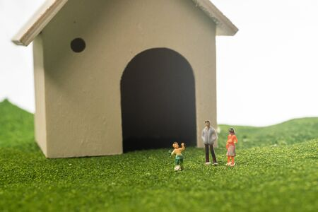 Miniature people in from of toy house. Happy family concept: a family in front of a house