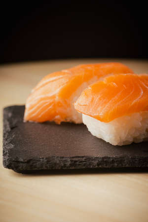 Salmon nigiri sushi, served on a black slate plate, selective focus