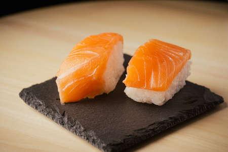 Salmon nigiri sushi, served on a black slate plate, selective focus