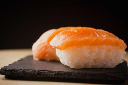 Salmon nigiri sushi, served on a black slate plate, selective focus Foto de archivo
