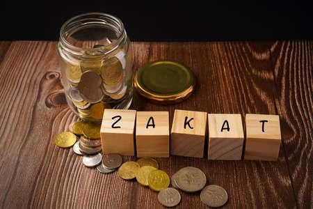 "Zakat Islamic Concept. ""ZAKAT"" wordings wih coins in jar on wooden background"