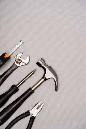 Flat lay composition of a set of tools, including hammer, pliers, wrench, screwdrivers and measuring tape. Top view, concept for father's day, including copy space