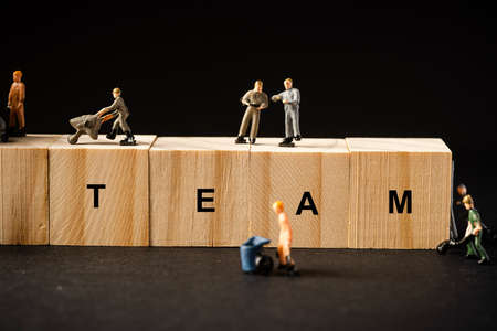 "Teamwork concept. Miniature builders figure with wooden blocks with ""TEAM"" wordings"
