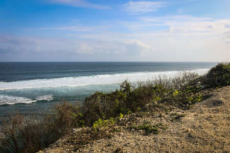 A wide angle shot at Pandawa Beach, Bali with parasols on sandy beach with strong waves at the ocean and a clody blue sky