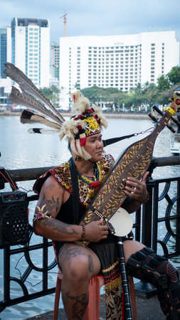 Sarawakian Man playing Sape, traditional Sarawak Musical instrument