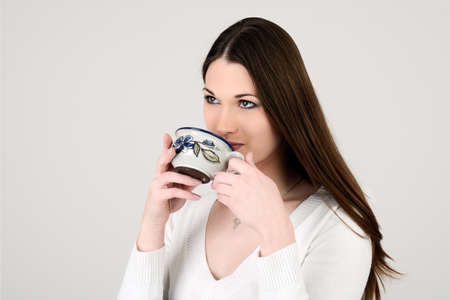 Young attractive white dressed girl drinking tea