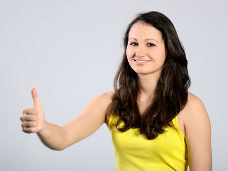 Young attractive girl with her thumb up