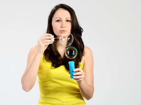Young attractive girl dressed yellow blowing big bubbles Stock Photo
