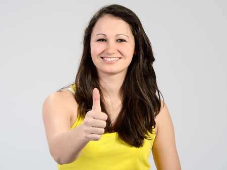 Young attractive smiling girl dressed yellow with her thumb up Stock Photo
