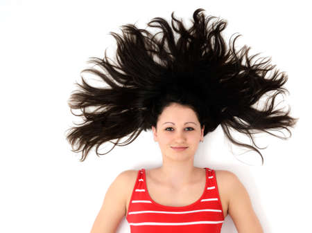 Young attractive girl lying on a white paper with tree shaped hair Stock Photo