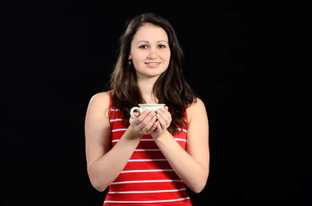 Young attractive girl holding a cup of tea or coffee