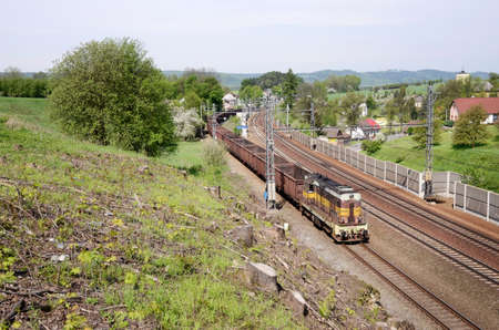 Old diesel cargo locomotive with empty coal rail cars Stock Photo