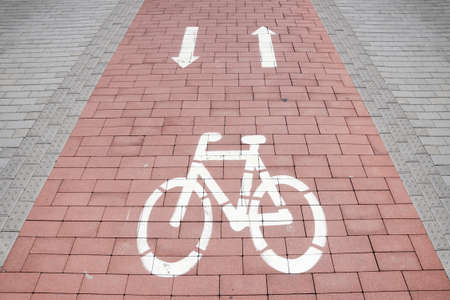 Paved bicycle trail in a town or city. White bicycle sign and two arrows Stock Photo