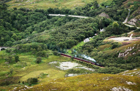 Touristic old train with steam locomotive in scottish countryside
