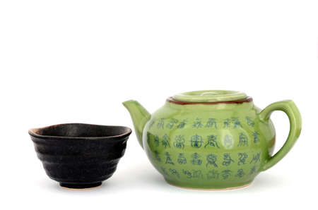 Green teapot and dark brown cup on whote background Stock Photo