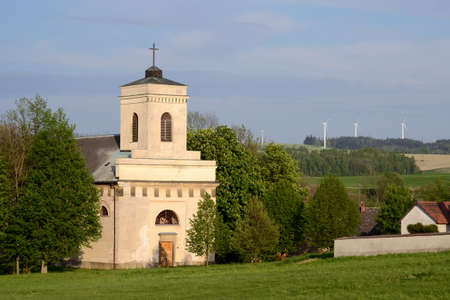 Church in village in the central Czech Republic, windmills in the background