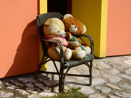Two big teddy bears sitting on a wooden chair in front of a house