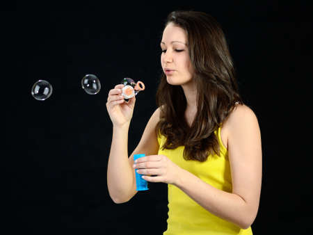 Pretty teenage girl blowing bubbles, black background