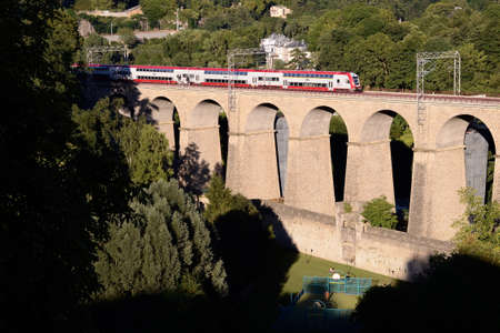 Passenger trainset on an old viaduct in Luxembourg city Stock Photo