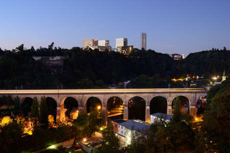 Old railway viaduct in Luxembourg with a train light line, modern buildings in background Stock Photo
