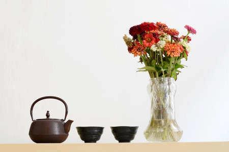 Iron teapot, two cups and vase with withered flowers Stock Photo