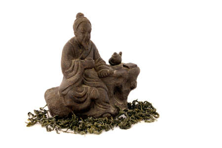 Japanese tea master statuette on white background and  with tea leaves around