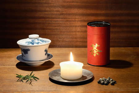 tea bowl, candle, tea box and tea leaves in warm colors