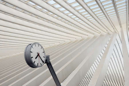 Modern railway building of glass and concrete with a round clock Stock Photo