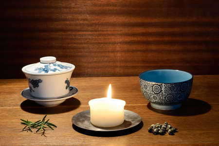 Tea bowl, gaiwan, candle, tea leaves in warm colours Stock Photo