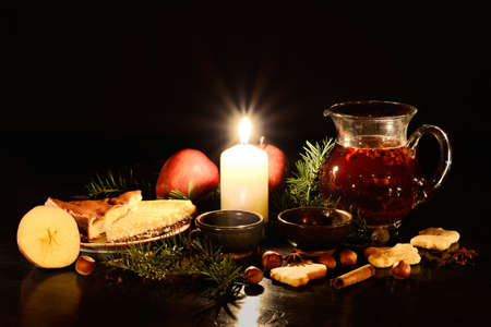 Christmas or winter still life with fruit tea, indian teacup, candle, cake, nuts, cookies, and branches