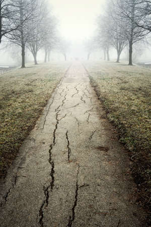 Cracky small road leading to the mist, photographed in winter Stock Photo