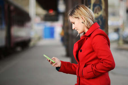 Woman in red coat watching her phone at a railway station