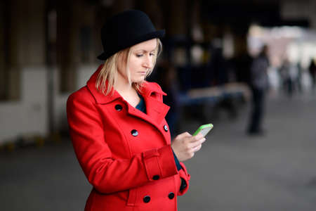Woman dressed in red waiting for a train, watching her phone
