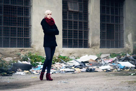 Young beautiful woman in fashion clothes taken in a dirty industrial area surrounded by rubbish