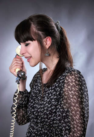 speaks: the young girl speaks      by phone  Stock Photo