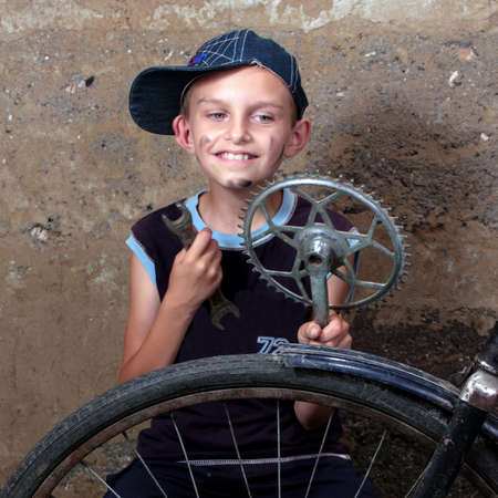 the boy repairs and old bikycle  photo